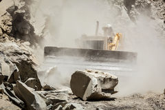 Bulldozer cleaning landslide on road in Himalayas Royalty Free Stock Images