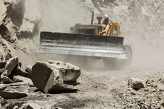Bulldozer cleaning landslide on road in Himalayas Stock Images