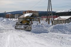 The bulldozer cleans the road from the snow on the street. The bulldozer cleans the road from drifting snow on the street in the village. Belogorsk. Kemerovo Stock Image