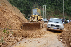 Bulldozer clears the road. NORTHERN LAOS - AUGUST 14: Bulldozer clears the road because of landslide on August 14, 2012 in Northern Laos. Landslides are common Stock Images
