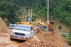 Bulldozer clears the road. NORTHERN LAOS - AUGUST 14: Bulldozer clears the road because of landslide on August 14, 2012 in Northern Laos. Landslides are common Stock Image