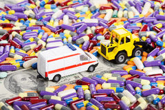 Bulldozer clears the way for the ambulance through the dollars a. Nd pills (installation on the theme of modern medicine trends royalty free stock photography