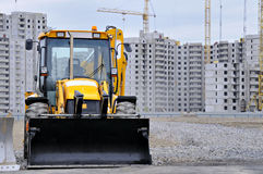 Bulldozer on construction of apartment houses. Building construction in new microdistrict of St.-Petersburg, Russia Royalty Free Stock Photos