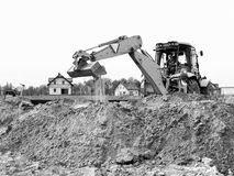 Bulldozer on construction site. Black and white view of bulldozer on construction site with houses in background Stock Photos