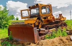 Bulldozer on construction site beneath cloudy sky Stock Photos