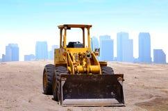 Bulldozer construction site buildings background. A yellow bulldozer is in a construction site with a city buildings background stock photos