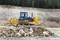 Bulldozer on the construction site of the road. The bulldozer moves and spreads the soil and rubble on the embankment of the road Royalty Free Stock Photography