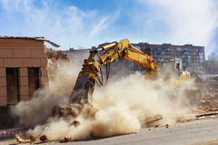 Building demolition. Bulldozer crushing the building at construction site Stock Images