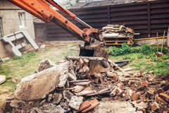 Bulldozer on demolition site working on building and loading bricks and concrete into dumper trucks. Bulldozer on demolition site working on old building and Royalty Free Stock Image
