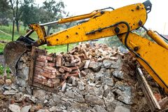 Bulldozer on demolition site working on an old building and load Stock Photos