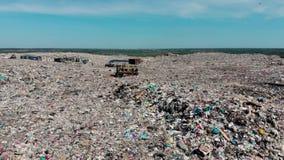Bulldozer die aan berg van huisvuil in stortplaats werken stock footage