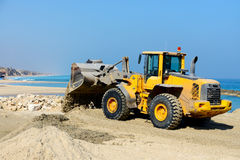 Bulldozer die aan een strand werken Stock Afbeeldingen