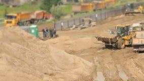 Bulldozer die aan grote stapel van zand in de zomer werken stock footage
