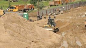 Bulldozer die aan grote stapel van zand in de zomer werken stock videobeelden