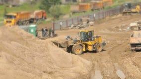Bulldozer die aan grote stapel van zand in de zomer werken stock video