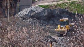 Bulldozer die bij de fabriek achter bloeiende bomen werken stock footage