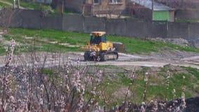 Bulldozer die bij de installatie achter bloeiende bomen werken stock video