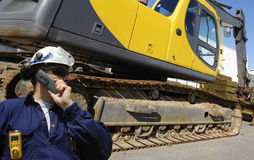 Bulldozer and driver. Giant bulldozer, digger, with driver in hard-hat,  talking in phone Stock Images