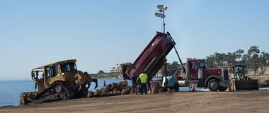 Bulldozer and Dump truck unloading dirt on Goleta Beach, Califor. Santa Barbara, United States - Febriary 16, 2018: Bulldozer and Dump truck unloading off stock photography