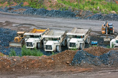 Bulldozer, dump trucks and excavator. At the bottom of the quarry royalty free stock images