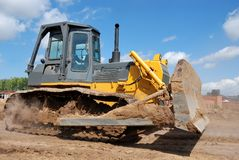 Bulldozer earthmover in action. Bulldozer loader at earthmoving works over brigt sky Royalty Free Stock Images