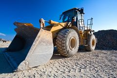 Bulldozer, excavator. Bulldozer or excavator, industrial machinery against the blue sky Royalty Free Stock Photo
