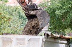 Bulldozer excavator loading ground to tipper truck on the street reconstruction site. stock photo