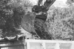 Bulldozer excavator machinery bucket loading ground to tipper truck on the street reconstruction site black and white with motion royalty free stock photography