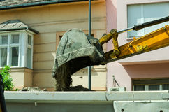 Bulldozer excavator machinery loading ground to tipper truck on the street reconstruction site royalty free stock photography