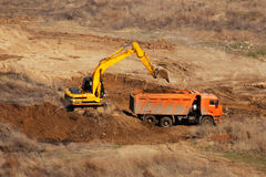 Bulldozer is gaining the earth in bucket and pours in truck Royalty Free Stock Images