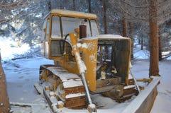 Bulldozer giallo coperto di neve abbandonata in foresta fotografia stock