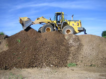 Bulldozer in a gravel pit. With a brilliant blue sky Royalty Free Stock Image