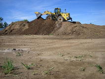 Bulldozer in a gravel pit. With a brilliant blue sky Royalty Free Stock Photography