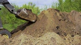 Bulldozer het leegmaken grond van emmer op de aardewerk met tuin op achtergrond stock videobeelden