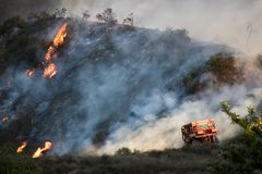 Bulldozer on Hillside with Burning Brush in Background During California Fire. Bulldozer working on hillside with flames and smoke in background during stock photo