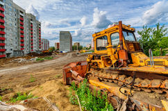 Bulldozer and houses beneath cloudy sky Stock Photo