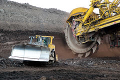 Bulldozer and huge mining excavator wheel in brown coal mine Royalty Free Stock Photography