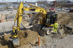 Bulldozer inside building site. Large bulldozer, digger, excavating inside construction-site, driver and engineer talking Royalty Free Stock Photo