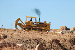 Bulldozer leveling ground and generating fumes Royalty Free Stock Image