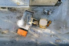 Bulldozer loader uploading waste and debris into dump truck at construction site. building dismantling and construction. Waste disposal service. Aerial drone royalty free stock image