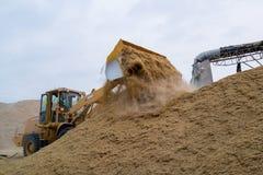 Bulldozer loading rice husk. Pijit, Thailand - March 31, 2013: Bulldozer loads rice husk in the rice mill Stock Images