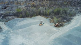 A bulldozer loads rubble in a stone quarry. Aero survey With quadrocopter stock video footage