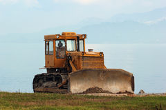 Bulldozer. A lone bulldozer with sea in the background Stock Photography