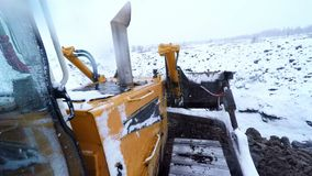 Bulldozer machine working with ground on snow winter day. View from cabin.  stock video