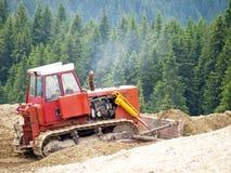 Bulldozer in mountains. Bulldozer working in wooden mountains Royalty Free Stock Photos