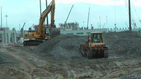 Bulldozer moves gravel on construction site stock video