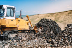 Bulldozer moving garbage with scoop. Industrial construction details Royalty Free Stock Photography