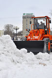 The bulldozer occupied with snow cleaning costs on the street in Stock Photos