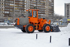 The bulldozer occupied with snow cleaning costs on the street in Stock Images