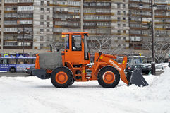 The bulldozer occupied with snow cleaning costs on the street in Royalty Free Stock Images